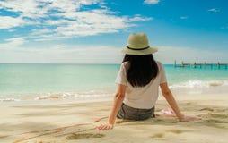 Gelukkige jonge vrouw die in witte overhemden en borrels bij zandstrand zitten Het ontspannen van en het genieten van van vakanti stock foto's