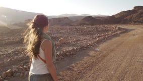 Gelukkige jonge vrouw die in woestijnweg lopen op zonsondergang met mooie zongloed Het Park van Timna, Israël stock videobeelden