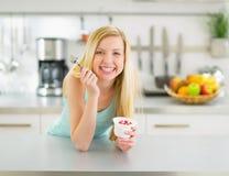 Gelukkige jonge vrouw die yoghurt in keuken eten stock afbeeldingen