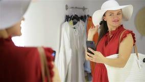 Gelukkige jonge vrouw die zich in montageruimte bevinden in kledingsopslag Het meisje neemt foto dichtbij kleedkamer stock video