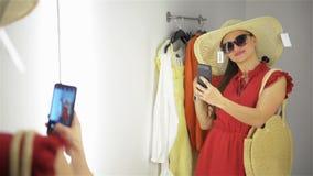 Gelukkige jonge vrouw die zich in montageruimte bevinden in kledingsopslag Het meisje neemt foto dichtbij kleedkamer stock footage
