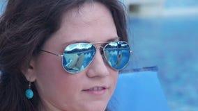 Gelukkige jonge vrouw die zonneschermolie dicht omhoog toepassen, glimlachend gezicht stock footage