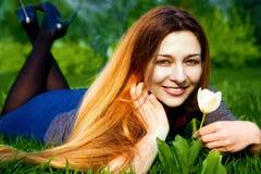 Gelukkige jonge vrouw en bloem in vers gras royalty-vrije stock foto's