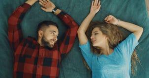 Gelukkige jonge vrouw en man dalingen op het groene bed in ruimte Minnaars die aan elkaar kijken stock video