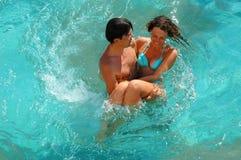 Gelukkige jonge vrouw en man in pool Stock Foto's