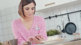 Gelukkige, jonge vrouw gebruikend smartphone en drinkend koffie in keuken stock footage