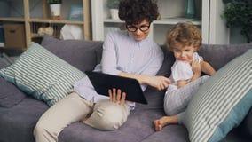 Gelukkige jonge vrouw gebruikend tablet en thuis spelend met haar kleine zoon op bank stock videobeelden