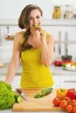 Gelukkige jonge vrouw het bijten komkommer terwijl het snijden van verse salade Royalty-vrije Stock Afbeeldingen