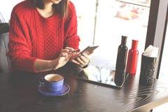 Gelukkige jonge vrouw het drinken cappuccino, latte, macchiato, thee, gebruikend tabletcomputer en sprekend op de telefoon in een royalty-vrije stock afbeelding