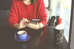 Gelukkige jonge vrouw het drinken cappuccino, latte, macchiato, thee, gebruikend tabletcomputer en sprekend op de telefoon in een stock foto