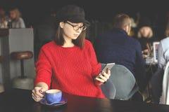Gelukkige jonge vrouw het drinken cappuccino, latte, macchiato, thee, gebruikend tabletcomputer en sprekend op de telefoon in een royalty-vrije stock foto