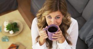Gelukkige jonge vrouw het drinken koffie in woonkamer royalty-vrije stock fotografie