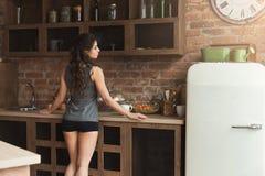 Gelukkige jonge vrouw het drinken ochtendkoffie in keuken stock foto