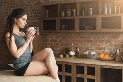 Gelukkige jonge vrouw het drinken ochtendkoffie in keuken royalty-vrije stock afbeeldingen