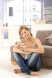 Gelukkige jonge vrouw het drinken thee thuis Royalty-vrije Stock Afbeeldingen