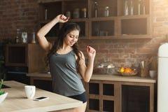 Gelukkige jonge vrouw het luisteren muziek in keuken royalty-vrije stock foto's