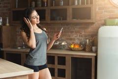 Gelukkige jonge vrouw het luisteren muziek in keuken royalty-vrije stock foto