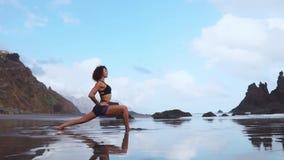 Gelukkige jonge vrouw het praktizeren yoga op het strand bij zonsondergang Gezond Actief Levensstijlconcept Langzame Motie stock videobeelden