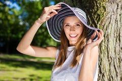 Gelukkige jonge vrouw in hoed die tegen boom buiten leunen Stock Afbeelding