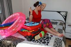 Gelukkige jonge vrouw in kleurrijke de zomeruitrusting dichtbij de rode bemande koffer Royalty-vrije Stock Foto