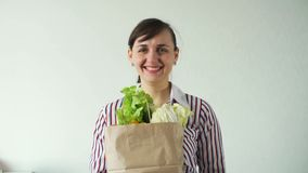 Gelukkige jonge vrouw met de zak van groenten stock footage
