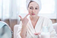 Gelukkige jonge vrouw met een handdoek op haar hoofd die haar huid in een spiegel bekijken Geschikte hygiëne en zorg voor de huid royalty-vrije stock afbeelding