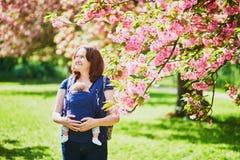 Gelukkige jonge vrouw met haar baby in drager stock fotografie
