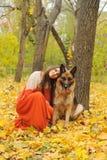 Gelukkige jonge vrouw met haar Duitse herdershond in de herfstpark stock foto's