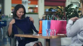 Gelukkige jonge vrouw met het winkelen zakken die nieuwe kleren tonen aan haar vriend stock video