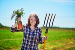 Gelukkige jonge vrouw met hooivork en rijpe organische wortelen Stock Fotografie