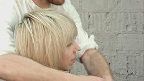 Gelukkige jonge vrouw met kapper het eindigen kapsel bij salon stock footage