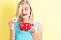 Gelukkige jonge vrouw met koekje en koffie stock afbeelding