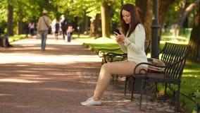 Gelukkige jonge vrouw met moderne smartphone in de zomerpark stock footage