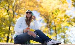 Gelukkige jonge vrouw met smartphone en hoofdtelefoons Royalty-vrije Stock Fotografie