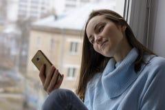 Gelukkige jonge vrouw met smartphone op de vensterbank dichtbij het venster van het huis, close-up royalty-vrije stock afbeeldingen