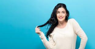 Gelukkige jonge vrouw op een stevige achtergrond Royalty-vrije Stock Foto