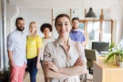 Gelukkige jonge vrouw over creatief team in bureau Stock Foto