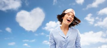 Gelukkige jonge vrouw in pyjama en oogslaapmasker stock afbeeldingen