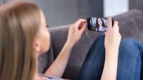 Gelukkige jonge vrouw twee die van video genieten die webcam samen gebruikend smartphoneclose-up babbelen stock videobeelden