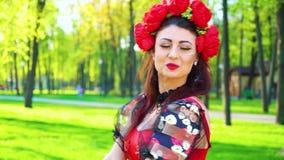 Gelukkige jonge vrouw in volks gestileerd kostuum die buiten met het effect van de lensgloed dansen stock footage