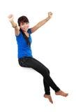 Gelukkige jonge vrouw in vrijetijdskledingszitting Royalty-vrije Stock Foto