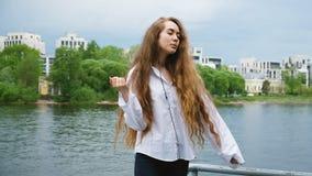Gelukkige jonge vrouw in wit overhemd met lang haar die in hoofdtelefoons dansen Europees aantrekkelijk meisje die aan muziek lui stock videobeelden