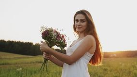 Gelukkige jonge vrouw in witte kleding die zich op gebied met boeket van bloemen in zonlicht bij zonsondergang bevinden stock video