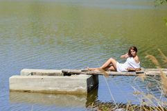 Gelukkige jonge vrouw in witte kledingszitting op pijler door rivier of meer Stock Afbeeldingen