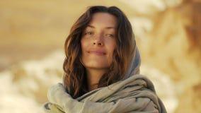 Gelukkige jonge vrouw in woestijncanion zij glimlacht en is, onderzoekt de camera benieuwd en rond stock video
