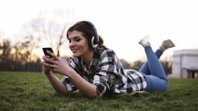 Gelukkige jonge vrouwelijke het luisteren muziek die op smartphone met hoofdtelefoons op groen gras in park liggen Meisje die pre stock footage