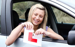 Gelukkige jonge vrouwelijke omhoog tearing bestuurder haar teken van L Royalty-vrije Stock Fotografie
