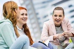 Gelukkige jonge vrouwelijke universiteitsvrienden die in openlucht bestuderen Stock Afbeeldingen