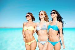 Gelukkige jonge vrouwen in bikinis over blauwe hemel en overzees royalty-vrije stock afbeelding