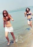 Gelukkige jonge vrouwen die bij het strand spelen Stock Fotografie